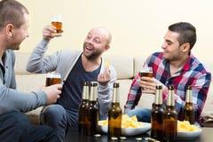 3 счастливых друз выпивая пиво Стоковые Фото