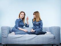 2 счастливых друз женщин нося говорить обмундирования джинсов Стоковое Изображение