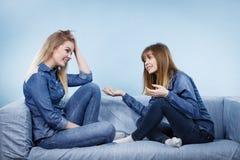 2 счастливых друз женщин нося говорить обмундирования джинсов Стоковая Фотография RF