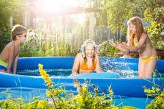 3 счастливых друз играя в раздувном бассейне Стоковая Фотография RF