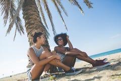 2 счастливых друз сидя на говорить пляжа Стоковые Изображения