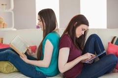 2 счастливых друз сидя спина к спине на книге чтения софы Стоковые Изображения RF