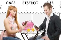 2 счастливых друз с телефонами в террасе кофейни Стоковое Изображение