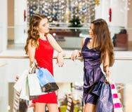 2 счастливых друз ходя по магазинам в моле 2 женщины стоя с сумками в платьях красных и сини Стоковые Фото