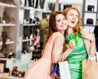 2 счастливых друз ходя по магазинам в моле Стоковые Изображения