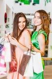 2 счастливых друз ходя по магазинам в моле Стоковое Фото