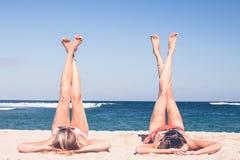 2 счастливых сексуальных друз женщин загорая на тропическом пляже Dua острова Бали, Nusa, Индонезия Стоковая Фотография