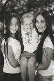 3 счастливых сестры обнимая и усмехаясь joyfully в парке лета Стоковая Фотография RF