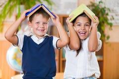 2 счастливых школьника имеют потеху в классе стоковые изображения