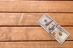 100 счетов доллара на таблице На деревянной предпосылке Стоковые Фото