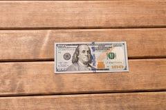 100 счетов доллара на таблице На деревянной предпосылке Стоковая Фотография RF