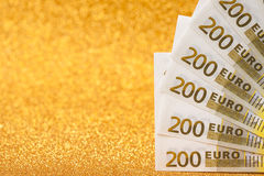 200 счетов евро на золотой сверкная предпосылке Много деньги, роскошь Стоковое фото RF