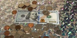 100 счетов США доллара окруженных стогами монеток Стоковые Изображения