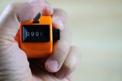 Счетчик бирки удерживания руки или машина подсчитывать с 0000 номерами, Стоковое Фото