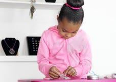 Счетчик ювелирных изделий маленькой девочки работая Стоковое Изображение
