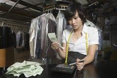 Счеты женщины расчетливые с калькулятором в прачечной Стоковое фото RF