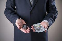 Счеты ключа и 100-доллара автомобиля в руках бизнесмена Стоковые Изображения