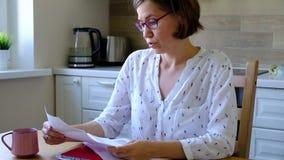 счеты над усилено Женщина Unpset смотря ее финансовые задолженности в кухне сток-видео
