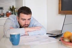 Счеты разочарованного человека расчетливые и расходы налога Стоковое фото RF