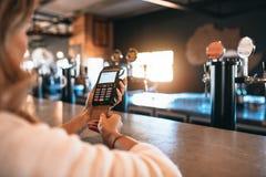 Счет женщины оплачивая используя кредитную карточку на баре Стоковое фото RF
