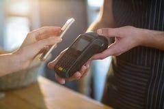 Счет женщины оплачивая через smartphone используя технологию nfc стоковое фото rf