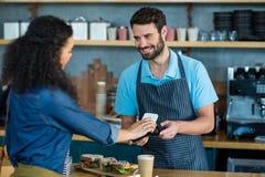 Счет женщины оплачивая через smartphone используя технологию nfc Стоковое Изображение RF