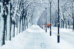 Счищатели в оранжевых жилетах идут вдоль снежного переулка стоковые фото