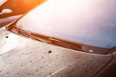 Счищатели лобового стекла серого автомобиля с падениями после идти дождь в лучах стоковое изображение rf