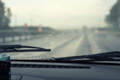Счищатели очищают лобовое стекло автомобиля от падений дождя автомобиль внутри взгляда стоковые фото
