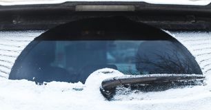 Счищатель автомобиля на заднем окне покрытом с снегом Стоковые Фото