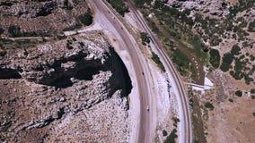 Съемка взгляда сверху воздушная красивой дороги и железнодорожных путей шоссе идя между изумлять скалистые гребни горы песчаника сток-видео