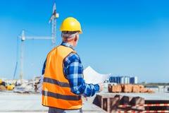 Съемка вид сзади построителя в отражательном жилете и защитном шлеме стоя на строительной площадке с зданием планирует Стоковые Изображения