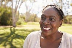 Съемка голов и плечи зрелой женщины в парке Стоковые Фото
