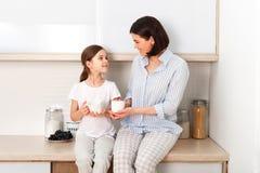Съемка жизнерадостной матери и дочь сидят совместно на кухонном столе, выпивают горячий чай в утре, имеют приятное дружелюбное стоковые изображения rf