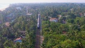 Съемка замедленного движения воздушная старый поезд едет через тропики с пальмами и виллами акции видеоматериалы