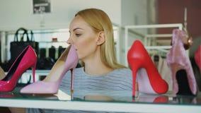 Съемка конца-вверх белокурой молодой женщины выбирая ботинки высоко-пятки в магазине обуви Она рассматривает различные пятки видеоматериал