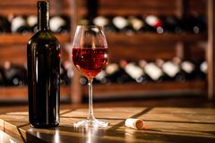 Съемка конца-вверх бутылки и стекла вина помещенных на деревянном столе Полки с бутылками вина на предпосылке Стоковое Изображение RF