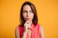 Съемка конца-вверх красивой думая женщины в красном платье, смотря Стоковое Фото