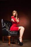 Съемка красивой женщины нося красное усаживание платья Стоковое Изображение