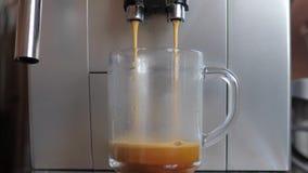 Съемка крупного плана от машины или кофеварки эспрессо льет кофе в стеклянной чашке видеоматериал