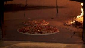 Съемка лотка шеф-повара кладя vegaterian пиццу в печь кирпича сток-видео
