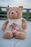 Съемка милого ребёнка с фиолетовым держателем пока спать и играть с большим плюшевым медвежонком на крыше/фокусируют на младенце  Стоковое Изображение RF