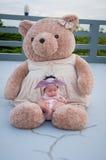 Съемка милого ребёнка с фиолетовым держателем пока спать и играть с большим плюшевым медвежонком на крыше/фокусируют на младенце  Стоковые Изображения