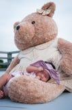 Съемка милого ребёнка с фиолетовым держателем пока спать и играть с большим плюшевым медвежонком на крыше/фокусируют на младенце  Стоковое фото RF