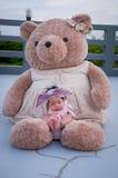 Съемка милого ребёнка с фиолетовым держателем пока спать и играть с большим плюшевым медвежонком на крыше/фокусируют на младенце  Стоковое Изображение