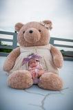 Съемка милого ребёнка с фиолетовым держателем пока спать и играть с большим плюшевым медвежонком на крыше/фокусируют на младенце  Стоковые Изображения RF