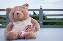 Съемка милого ребёнка с фиолетовым держателем пока спать и играть с большим плюшевым медвежонком на крыше/фокусируют на младенце  Стоковое Фото