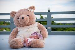 Съемка милого ребёнка с фиолетовым держателем пока спать и играть с большим плюшевым медвежонком на крыше/фокусируют на младенце  Стоковая Фотография