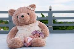 Съемка милого ребёнка с фиолетовым держателем пока спать и играть с большим плюшевым медвежонком на крыше/фокусируют на младенце  Стоковые Фото