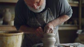 Съемка наклона-вверх профессионального гончара создавая опарник от коричневой глины в рабочем месте используя бросать-колесо гонч видеоматериал